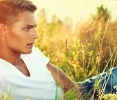foto of natural blonde  - Handsome guy lying on the field - JPG
