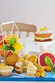 stock photo of curd  - Citrus Victoria Sponge Cake with Lemon Curd and variety of fresh citrus fruits - JPG