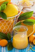 image of curd  - Lemon curd in a small jar with fresh citrus fruits and leaves - JPG