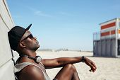 stock photo of sunbather  - Side view of relaxed african man leaning to a wall at beach sunbathing - JPG