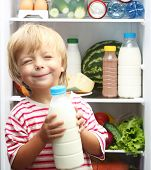 pic of refrigerator  - Happy little boy with milk against refrigerator with food - JPG