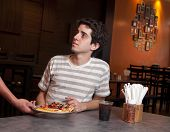 image of pizza parlor  - Young adult in a restauran receiving a slice of pizza - JPG