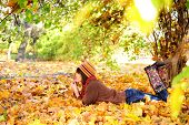 foto of stomach  - Woman lying on her stomach on autumn leaves in park - JPG