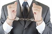 stock photo of handcuff  - Withe collar crime wih handcuffs elegant on withe background - JPG