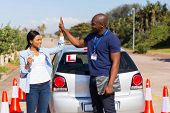 picture of driving school  - happy african girl and driving instructor doing high five after getting her driving license - JPG