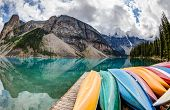 foto of tens  - A fisheye view of Moraine Lake in the Canadian Rockies with vibrant colored canoes on the foreground and the Valley of the Ten Peaks in the background - JPG