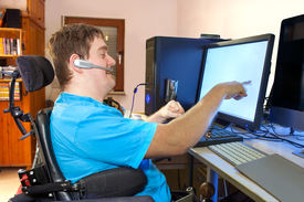 stock photo of touching  - Spastic young man with infantile cerebral palsy caused by a complicated birth sitting in a multifunctional wheelchair using a computer with a wireless headset reaching out to touch the touch screen - JPG