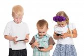 stock photo of fascinator  - Fascinated by the brothers and sister using smartphones - JPG