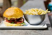stock photo of ground-beef  - Tasty burger with melted cheese and a thick succulent ground beef patty garnished with lettuce - JPG