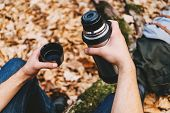 image of thermos  - Traveler man holding a cup of tea or coffee and thermos in autumn forest - JPG