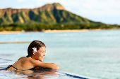 stock photo of waikiki  - Hawaii beach travel vacation woman swimming relaxing at luxury pool hotel resort - JPG