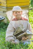 image of beehive  - Young beekeeper boy with painted wooden beehives - JPG