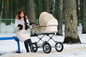pic of buggy  - reading book young mother with baby buggy  - JPG