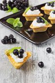 foto of mountain-ash  - canape with cottage cheese black berries of mountain ash and fresh mint leaves on a white wooden background - JPG