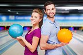 foto of bowling ball  - Cheerful young man and women looking over shoulders and holding bowling balls while standing against bowling alleys - JPG