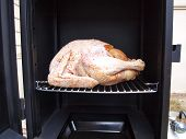 picture of smoker  - a whole turkey being cooked in a propane smoker grill - JPG
