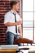 pic of tied  - Handsome young man in shirt and tie holding coffee cup and looking through the window while sitting at the window sill - JPG