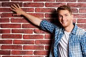 image of toothless smile  - Handsome young man touching a brick wall and smiling - JPG