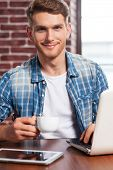 picture of toothless smile  - Handsome young man holding coffee cup and smiling while sitting at his working place - JPG