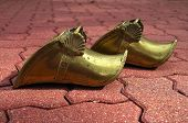 foto of gaucho  - A pair of gold gaucho stirrups against a brick walk - JPG