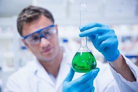 stock photo of beaker  - Chemist holding up beaker of green chemical in the laboratory - JPG
