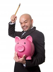 stock photo of spanish money  - bald Hispanic businessman with hammer in his hand holding pink piggybank ready to break the piggy bank and take money and savings out isolated on white background - JPG
