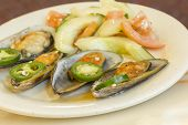 stock photo of jalapeno  - Spicy chili mussels with jalapeno slices and cucumber tomato salad - JPG