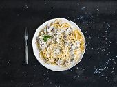 picture of pasta  - Pasta spaghetti with creamy mushroom sauce and basil in white ceramic plate over old grunge dark table - JPG