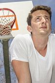 foto of early 20s  - Young man resting after exhausting basketball game - JPG