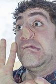 pic of lunate  - Crazy lunatic man smooshes face against glass surfaces - JPG