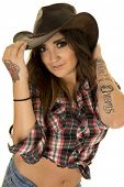 foto of cowgirl  - A cowgirl in her plaid top and western hat with her tattoo on her arm - JPG