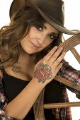 stock photo of cowgirls  - A cowgirl with her head close to a wagon wheel her hand on the wheel - JPG