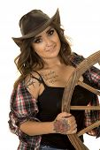 image of cowgirls  - A cowgirl with her hand on the wheel with a smile and her tattoos showing - JPG