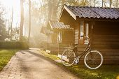 stock photo of log cabin  - Log cabins and a bicycle at sunrise - JPG