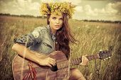 image of hippy  - Romantic girl in a wreath of wild flowers travelling with her guitar - JPG