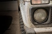 stock photo of monster-truck  - Muddy white vehicle covered in dried mud and headlamp with copyspace - JPG
