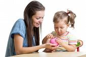 stock photo of coins  - Mother and daughter child putting coins into piggy bank - JPG