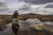 picture of boggy  - Man traveler on marshland against the backdrop of rain clouds - JPG