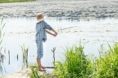 picture of chums  - Full length portrait of angler boy throwing bait of wooden green fishing rod - JPG
