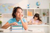 image of schoolgirl  - Portrait of dreamy Vietnamese schoolgirl sitting in the class - JPG