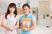 foto of  preteen girls  - Portrait of two cheerful preteen girls holding textbooks - JPG