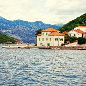 stock photo of stone house  - Old fishing village with pier and traditional mediterranean stone houses in the Kotor Bay - JPG