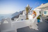 pic of ethereal  - A young beautiful blond bride stands on a fabulous balcony with beautiful wooden roof in a luxury hotel in a white wedding dress unique in Santorini on the background of the sunny sky with a long ethereal veil very moved by the wind - JPG