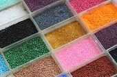 foto of beads  - Small decorative colorful beads in plastic containers - JPG