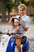picture of vespa  - Little blond boy sitting on the scooter with his mother - JPG