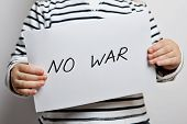 stock photo of war terror  - No war text written on paper held by a child - JPG