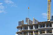 stock photo of formwork  - Crane hoisting formwork over construction site work - JPG