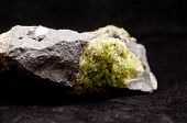picture of peridot  - olivine mineral sample with peridot and granite
