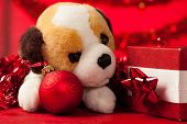 pic of christmas dog  - Toy dog plush puppy with christmas ornaments over red - JPG