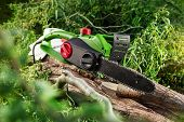 stock photo of chainsaw  - photo of modern green electrical chainsaw in forest - JPG